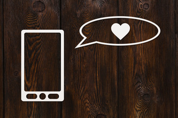 Paper tablet or smartphone and speech bubble with heart