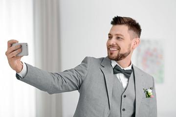 Happy groom taking selfie at home