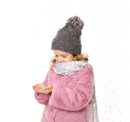 Cute little girl in warm clothes playing with snow on white background