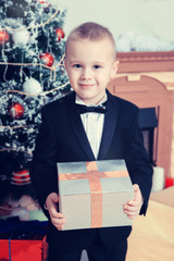 Boy near a Christmas tree with a gift in hand.