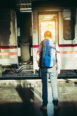 Portrait of a young man traveler waiting for train at platform. Travel concept.