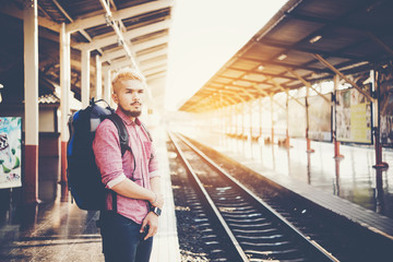 Young hipster man walking in platform looking away while waiting for the train at the railway station. Travel concept.