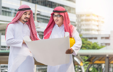 Arab businessman. Low angle view of Arab businessman and builder with blueprint looking away, Engineering Business Concept.
