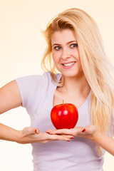 Happy woman holding delicious red apple