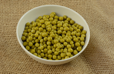 Canned low salt sweet peas in white bowl on burlap