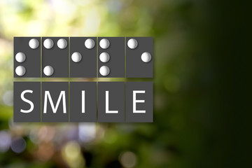 Black and White of Braille Alphabet meaning of SMILE on Color Bokeh Blur Background.