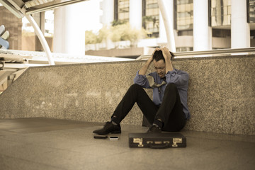Depressed man sitting on floor head in hands with city background.Unemployment concept