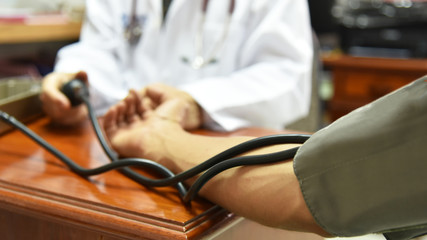 Close-up of measuring blood pressure by doctor.