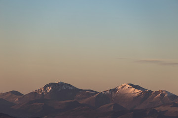 A minimalist view of some mountains top with snow, under a big, almost empty sky, with golden hour warm colors