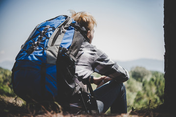Young tired hiker with backpack sitting on the mountain top while resting after active walk.