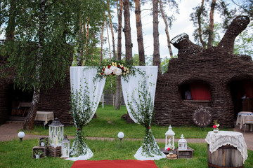 Beautiful wedding ceremony outdoors. Decorated chairs stand on the grass. Wedding arch made  flowers on a green natural background. Old doors, rustic style.