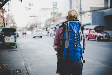 Young hipster traveling backpacker around asia. Holiday tourist concept.