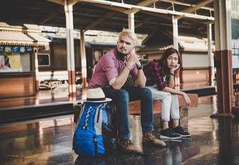 Young hipster couple sitting on wooden bench at train station. Couple sitting waiting for the train at platform.