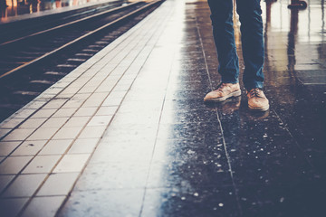 Feet of a young man wearing jeans who is waiting for the train at the platform of the train station.
