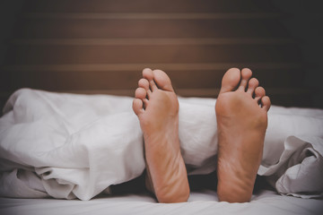 Men's feet under a blanket.