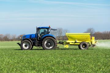 Traktor mit Düngerstreuer auf dem Feld - 6638