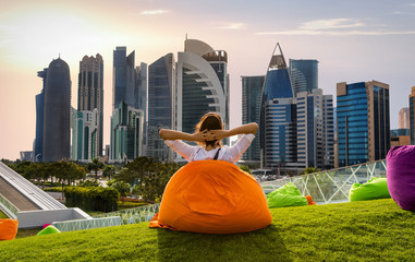 Frau auf Sitzkissen vor der Skyline von Doha, Katar