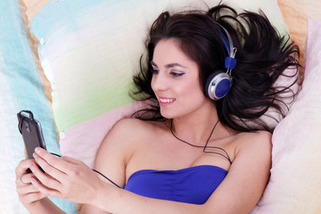Pretty girl listening to music relaxing in her coloured bed with her smartphone