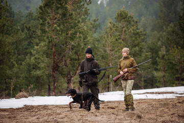 two hunters armed with a rifles, walking in a snowy winter forest.