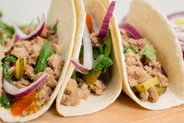 Mexican tacos with pork, pepper and tomatoes on the white wooden background. Shallow depth of field.