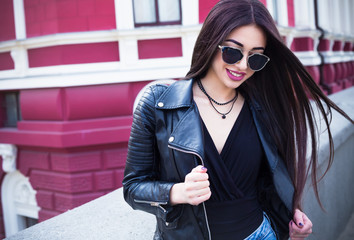 Outdoor lifestyle fashion portrait of young stylish hipster woman walking on street,wearing cute trendy outfit.Young woman with long dark hair  smiling to camera in city on city bulding background.