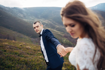 Groom looks at bride holding her hand on windy mountain hill