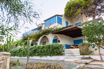 Classical architecture of the mediterranean cyprus, spaine, greek or italian white house with blue wooden windows and green trees, summer time