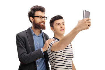 Young man and a teenage boy taking a selfie together