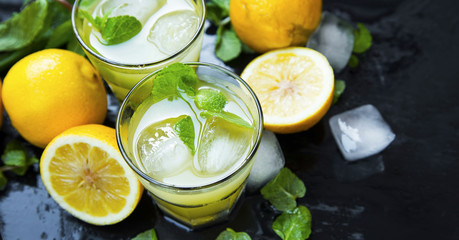Lemon cocktails with mint and ice cubes on dark background, mojitos ingredients