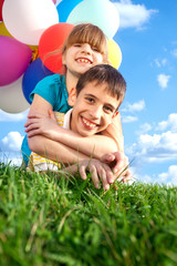 happy smiling children lying on the green grass with colorfull balloons in the background