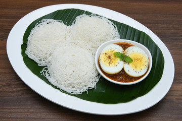 Noolappam/Idiyappam/rice noodles, a popular traditional steam cooked Kerala breakfast dish with hot and spicy egg roast curry on a houseboat, Alleppey, India. South Indian food. noolputtu Sri lankan