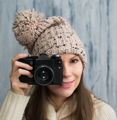 Beautiful lady in a hat with old camera