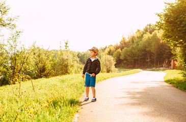 Little boy in straw hat walks on countryside road at the summer evening
