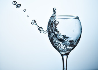 Water splashing out of a tall wine glass.