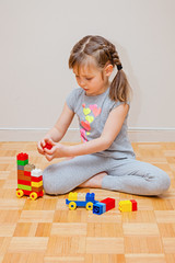 Six years old little girl playing with building blocks toys. Construction activity at home.