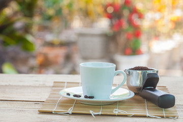 cup of coffee on disk and coffee scoop