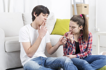 Teenage couple smoking. Boy lighting a cigarette