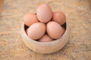 Egg in a wooden bowl on wooden table