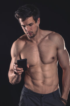 Handsome shirtless muscular young man using cell phone