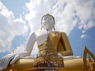Low angle of giant Buddha statue at Wat Phra That Doi Kham (Temple of the Golden Mountain) in Chiang Mai, Thailand