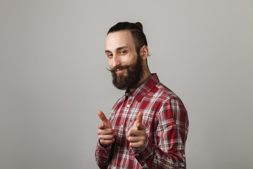 Bearded handsome cheerful man in red squared shirt on grey background