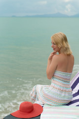 Young blonde woman on a beach lounger