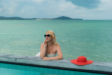 Young woman suntanning near swimming pool