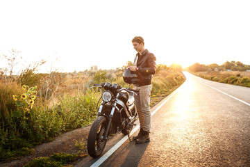 Young handsome man posing near his motorbike at countryside road. Flare sunlight background.