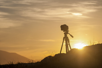 Photo camera at sunset in the mountains