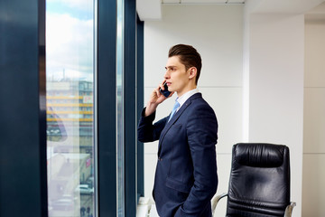 Brunet businessman talking on the phone in a business office.