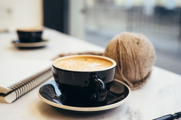 Cappuccino, envelope, ball of yarn pen and notebook on white marble tabletop.