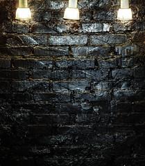 Light of three lamps on a black brick wall