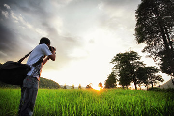 Young photographer on a wheat field