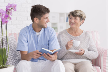 Professional carer reading to senior